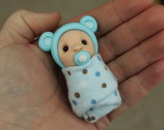 This listing is for one (1) hand sculpted polymer clay baby. She is 2 long and wrapped tightly in a soft fabric blanket. Great for indoor fairy gardens, keepsakes, gifts and cake toppers! ******************* Each figurine is made entirely by me from start to finish. They are sculpted individually so no two will ever be exactly the same. Select areas/features (such as eyes or accessories) on my figures are highlighted with a gloss sealer to enhance their appearance. These original pieces...