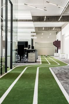 Office for a football app company featuring turfed meeting rooms and a running track.