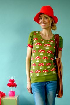Kurzarmshirt aus olivfarbnem Jersey mit einem Pilzmuster in rot-grün. Hinten ist es einfarbig oliv.  Auf dass der Frühling nicht mehr weit entfernt...