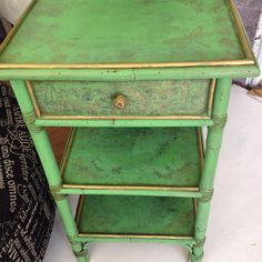 Reworking a vintage table in a Annie Sloan Antibes Green, wax and gold gilding.  Gold stamped lotus and dragon fly on shelfs and drawer front.
