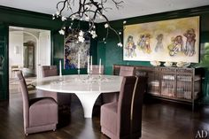 In the dining room of a Connecticut home, a bespoke light sculpture by David Wiseman from R 20th Century is suspended above the Fox-Nahem–designed table and chairs, the latter upholstered in a Knoll Luxe fabric; a Christophe Côme sideboard from Cristina Grajales Gallery stands beneath a Richard Prince canvas.