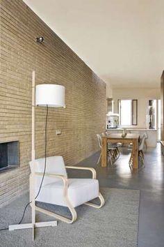 LUFTIG FORMSPRÅK: De stilrene møblene i tre og hvitt gir en letthet til rommet. Sammen med murveggen og betonggulvet blir det en kul miks av materialbruk.