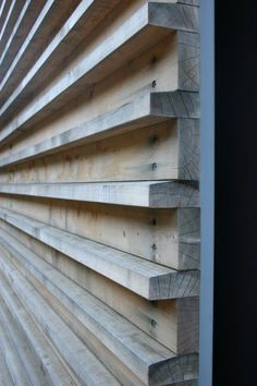 Gorgeous wood wall made of wood slats connected to a substrate. Note the angling at the top of the projecting pieces, so water sheds off the wood.