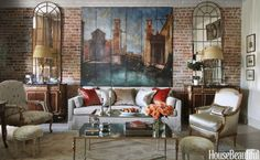In the living area of a New Orleans loft, the 19th-century screen with a painted scene of Venice defines the color scheme. Designer Lynne Uhalt looked for furnishings that would reflect light, including a pair of French mirrors and iron coffee tables with antiqued mirrored tops. A Louis XVI bergère, seen at right, is accessorized with a B. Viz Design pillow. At left, an antique French chair is covered in a Zoffany fabric. The rug is an antique Oushak.