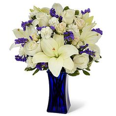 The Beyond Blue Bouquet brings together gorgeous white Asiatic Lilies, white roses, and white mini carnations accented with blue statice, cream spray roses, and lush greens. Presented in a dark blue glass vase to contrast with it's bright white blooms, this beautiful flower arrangement will make an excellent thank you, get well, engagement or sympathy gift.  Bouquet sizes are approximate.