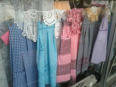 A happy little row of gingham aprons in the window of an antique store.