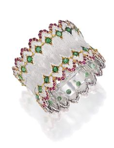 18 KARATTWO-COLOR GOLD, EMERALD AND RUBY BANGLE-BRACELET, BUCCELLATI. Set with 36 round emeralds weighing approximately 9.00 carats, bordered by numerous round rubies weighing approximately 4.50 carats, gross weight approximately 46 dwts, internal circumference 6 3/8 inches, signed Buccellati.