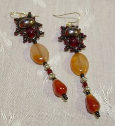 """An original design by KnotGypsy - Simply fun!  Earrings are hand knotted with nylon cord in black.  Beads include seed beads and other glass beads in red/amber...and some agate flat ovals/teardrops.  Earrings hang 3 inches from gold-filled ear wires.  I      design my jewelry to be durable as well as beautiful.  One of the      things I love about beaded micro macrame jewelry is that it feels so      """"friendly"""" in the hand and is comfortable to wear."""