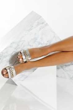 Handmade of fine quality calf leather, Ekavi slide sandals come in silver with gold details, gold, black, black with white, camel (waxed nubuck), blue (nubuck) with gold, and white with silver details. Ekavi design features a supportive thick strap decorated with our signature hand-woven chain. Wear this minimalist yet unique pair of slides with everything from palazzo pants to summer dresses. Greek Chic Handmades flat sandals are designed & handcrafted in Athens, Greece. Find your perfect… Boho Sandals, Silver Sandals, Greek Sandals, Leather Sandals Flat, Flat Sandals, Comfortable Flats, Leather Dresses, Slingback Sandal, Toe Rings