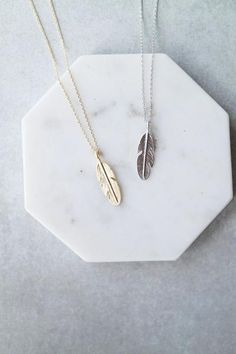 "A delicate chain with a simple feather pendant. Details: - 15 1/2"" + 1 1/4"" extender - Lobster clasp closure - Plated metal - Handmade"