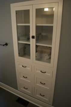 idea for bathroom - in place of dble door... nice built in, glass doors, drawer pulls