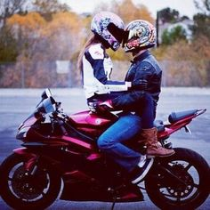 A biker and biker girl on one bike, and it looks that they are in love.