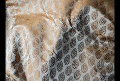 This is a beautiful silk brocade floral design fabric in Brown and Gold. The fabric illustrate small golden woven leaves on Brown background.  You can use this fabric to make Dresses, Tops,...