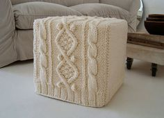 A hand-knit cover transforms a mod square ottoman into a homelike hassock.