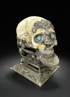 An impressive silver-mounted ceremonial Skull Bowl (kapala mandala)  Tibet or Nepal, 19th Century  in three sections, the skull with silver nose, teeth, bulging silver eyes set with turquoises, the forehead with a silver lotus swag, the cranium carved with sanscript, the silver bowl at the base of the skull with repoussé decoration consisting of a conch shell, dragons, scrolls and lotus palmette