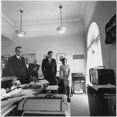 Attorney General Robert Kennedy, McGeorge Bundy, Vice President Lydon Johnson, Arthur Schlesinger, Admiral Arleigh Burke, President John F. Kennedy and Mrs. Jacqueline Kennedy watch NASA astronaut Alan B. Shepard on television. Shepard is striding across the deck of the U.S. Navy carrier Lake Champlain following an inspection of his spacecraft on May 5, 1961. He had just completed the first manned suborbital flight in the Project Mercury Program.