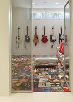 """The ultimate """"music"""" room - guitar collection on the wall and an album floor"""
