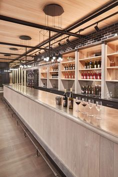 This contemporary wine tasting room has a custom made forty feet long (20m) pewter-topped, pine based bar is the focal point of the room. Black geometric light fixtures hang above the bar breaking up the neutral tones of the space.