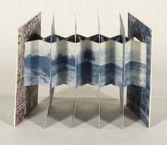 """Loom by Carol Barton, 1989 """"Tunnel book of six sections with textile patterns surrounding images of the Earth and space. Enclosed in a clear plastic box."""""""