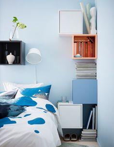 Sengebord lavet af farverige, kvadratiske skabe og hylder monteret på væggen omkring en seng
