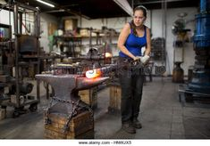 Female metalsmith turning red hot metal rod on workshop anvil - Stock Image