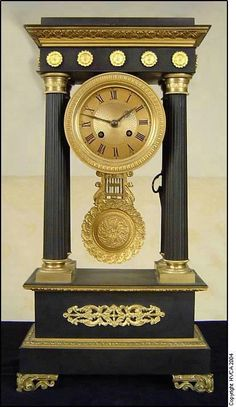 FRENCH EMPIRE MANTEL CLOCK A 19th century French Empire gilt bronze and patinated four column clock by Marti.