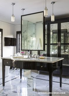 Hollywood glam ensuite bathroom with black built-in floor to ceiling bathroom cabinets with antiqued mirrored doors and flatscreen TV. Glossy black washstand with granite countertop and hanging black mirror. Marble bathroom floor paired with black marble border floor tiles.