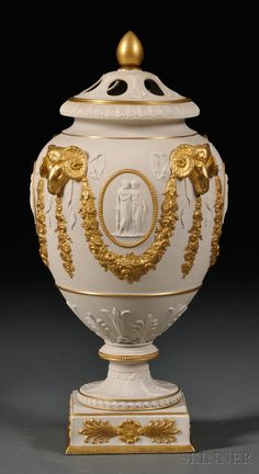 Wedgwood Gilded White Stoneware Potpourri Vase and Cover, England, 19th century, ram's heads supporting floral festoons surrounding classical medallions, pierced cover.