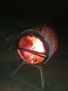 Looks like a repurposed dryer drum into a sideways firepit. The more I think about it, it's genius. Safer for windy areas, the fire gets more oxygen, you can sweep up the ashes, and best of all, it's recycled!