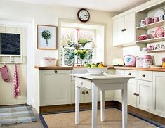small, white kitchen with wood countertops and large wood knobs, desk island