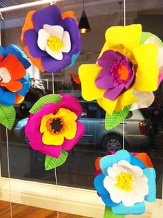 Instead of fixing them onto walls, why not hang them? Give the passersby a teasing peek at this colorful paper flowers suspended near large glass windows!