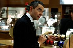 Rufus (ROWAN ATKINSON), indispensable behind a department store counter, in Richard Curtis' romantic comedy Love Actually. Emma Thompson, Liam Neeson, Colin Firth, Alan Rickman, Andrew Lincoln, Keira Knightley, Working Title Films, Dna, Love Actually 2003