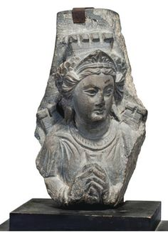 AN ALLEGORICAL FIGURE OF A CITY (TYCHE) GANDHARA, CIRCA 2ND/3RD CENTURY The carved grey schist relief depicting a bejewelled woman wearing a toga and joining her hands together, crowned by a tiara and a model of walled city, crenelated walls rising from her shoulders, on old wooden stand, the underside with old label 9½in. (24.1cm.) high (with stand)