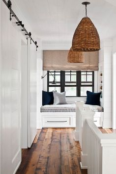 Farmhouse landing with shiplap, window seat reading nook, barn door, and rustic wide plank hardwood floor. Jennifer Worts Design Inc