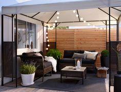 Terrasse med havesofaer og havebord af sortbrun plastrotting med sorte hynder, under pavillon