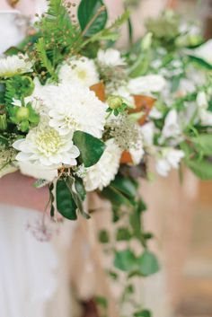 Bridal bouquet made with white dahlias, Queen Anne's Lace and magnolia leaves. Bouquets by Moonflower, image by Rustic White Photography. Featured in the Fall 2014 issue of Weddings Unveiled.