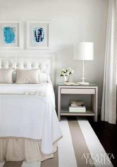 White and beige bedroom features turquoise art in see through picture frames placed above a white tufted headboard on bed dressed in white and beige Greek key bedding and a beige bedskirt placed next to a beige nailhead nightstand, Bernhardt Weston Nightstand, atop a white and beige striped rug.