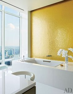 The wall in this master bathroom is embellished with gold-leafed glass-mosaic tile | archdigest.com