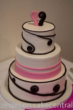 "First wedding cake - I've done it, I am no longer a wedding cake virgin! This was for my lovely friend who told me she trusted me, to do whatever I wanted and she would love it. It's 12"", 9"", and 6"". Their colours were hot pink and chocolate. So the pink stripes are for her, she's a bit of a barbie doll, and a neat freak so the neat pink stripes suit her..hehe.. The brown koru are for him. He's maori, and koru are a commonly used shape in maori art."