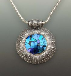 Pendant moulded from a sea urchin with stunning blue dichroic glass fused into the centre by Joy Funnell.