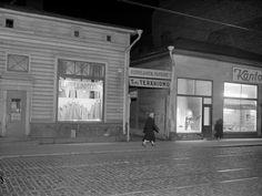 Kuvassa vuonna 1955 asumiskelvottamana purettavaksi määrätty puutalo Iso Roobertinkatu 20-22:ssa. Rakennuksen liikkeissä on loppumyyntejä. H...