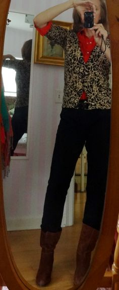 Dressing over 50, black pants, brown boots, a flash of red and animal print sweater.