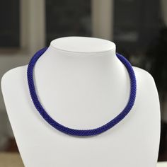Unique handmade blue bead necklace made of blue beads and white thread.
