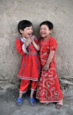 Faces of Afghanistan, 2 little boys dressed in traditional red, leaning against a wall and laughing.   ~  by O.Blaise, via Flickr