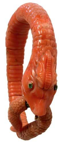 10      A 19th century carved coral bracelet, formed as a coiled serpent with gold set emerald eyes.