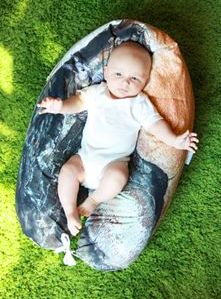 the organic nursing pillow can be formed to a very cosy, comfortable and solid nest for babies. the special tying technique allows to use the pillow for several situations. sketched squirrel is resting on a pine bark. NESTHOCKER. photographed by von ERIKA.