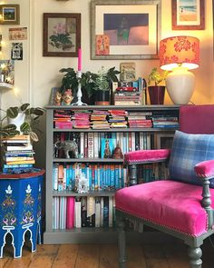 Eclectic living room, bookshelf, pink armchair. Love the fabric lampshade.