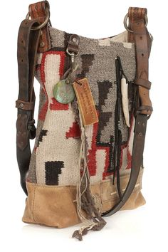 Masterfully crafted from vintage Navajo wool blankets and leather chaps, Ralph Lauren Collections' hand-loomed hobo bag exudes authentic Americana appeal. Decorated with luggage tags and sporadically sewn metal studs and glass beads, each carryall is stunning in its individuality.