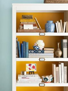 paint the back of a bookcase for a pop of color, love this mustard with the gold labels on the shelves.