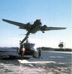 """May 26, 1968 I landed at Dong Tam due to a hydraulic failure. The tower asked me to """"land long,"""" so I did. Since their ground handling wheels were broken, the tower re-opened the runway. This Caribou did a fine job of missing us as it took off. The guy on the right is unknown; the shirtless guy is doorgunner SP4 Dennis Akers. Dennis was KIA nine days after this photo was taken. He died in the crash of helicopter #65-10019 after it was hit by a rocket propelled grenade."""